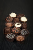 Variety of handmade chocolates. Assortment of finest selection chocolates on a dark wooden background royalty free stock photo