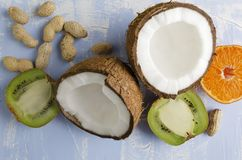 Fresh healthy veg food.Coconut,peanuts,kiwi fruit,orange on blue background stock photos