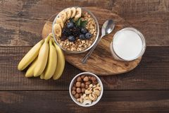 Variety of healthy breakfast of muesli with berries and nuts. Variety of healthy Breakfast of muesli with berries, nuts, bananas and glass of milk on wooden royalty free stock photography
