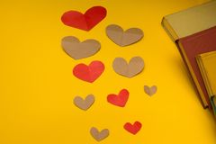 A variety of heart and books on a yellow background stock photo