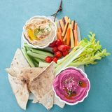 Variety of homemade hummus. With fresh vegetable sticks Royalty Free Stock Images