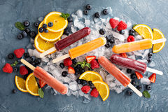 Variety of ice popsicles with fruits. Variety of healthy ice popsicles with fruits and berries on ice royalty free stock image