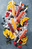 Variety of ice popsicles with fruits. Variety of healthy ice popsicles with fruits and berries on ice royalty free stock photography