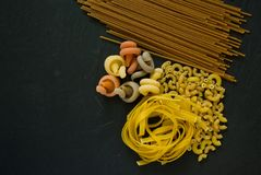 Variety of italian uncooked pasta flat lay on a black background stock image
