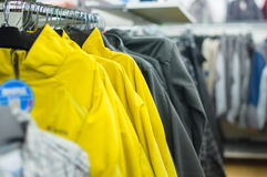 Variety of jackets, vests and sweaters on stands Royalty Free Stock Photos