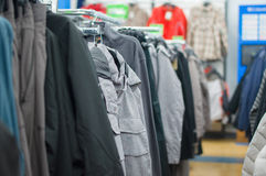 Variety of jackets, vests and sweaters on stands Stock Photos
