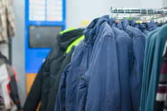 Variety of jackets, vests and sweaters on stands Stock Photography