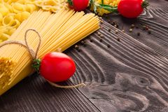 Variety of kinds and forms of dry macaroni with tomatoes and rosemary. Italian macaroni raw food or texture: pasta royalty free stock image