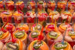 Variety kinds of fresh fruits in plastic cups preparing for smoothie drinks royalty free stock image