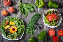 A variety of leafy greens with sliced peaches and tomatoes stock images