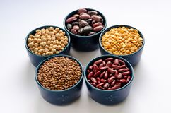 A variety of legumes. Lentils, chickpeas, peas and beans in blue bowls on a white background. Close-up royalty free stock photo