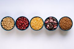A variety of legumes. Lentils, chickpeas, peas and beans in blue bowls on a white background. Top view stock photo