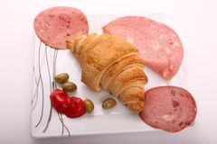 Luncheon meat with croissant. Variety of luncheon meat on dish with white background Stock Photo
