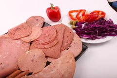 Variety of luncheon meat with salad. Variety of luncheon meat on modern black dish over white background Royalty Free Stock Photos