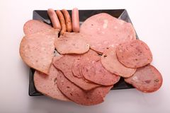 Variety of luncheon meat. On modern black dish over white background Royalty Free Stock Photo