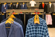 Variety of male clothes hanging on rack in boutique Stock Images