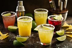 Variety of margarita cocktails. With salted rim and lime on dark background royalty free stock image