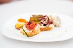 Variety of meat and fish canapes. On a white plate stock photo