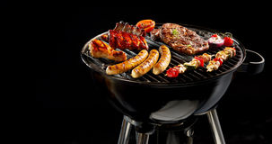 Variety of meat grilling on a portable barbecue. Variety of different meat grilling on a portable barbecue over a dark background with copy space in panoramic Stock Photo