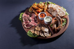 Variety meats with sauce. On a wooden platter with a contrasting light Royalty Free Stock Photos