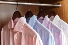 Variety of men`s shirts on a wooden hangers Royalty Free Stock Photography