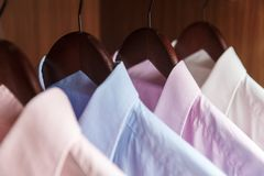 Variety of men`s shirts on a wooden hangers Royalty Free Stock Photo