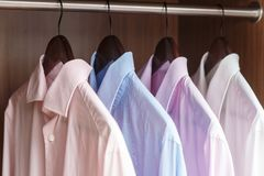 Variety of men`s shirts on a wooden hangers Stock Images