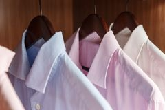 Variety of men`s shirts on a wooden hangers Stock Photo