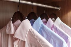 Variety of men`s shirts on a wooden hangers Royalty Free Stock Images