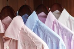 Variety of men`s shirts on a wooden hangers Royalty Free Stock Image
