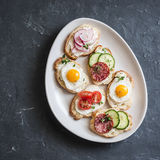 Variety of mini sandwiches with cream cheese, vegetables, quail eggs and salami. Sandwiches with cheese, cucumber, radish, tomatoe Stock Images