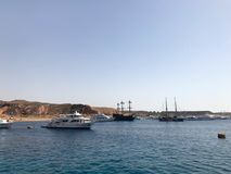A variety of motor and sailing ships, boats, cruise liners stand on a dock in the port against the background of the blue sea and royalty free stock photography
