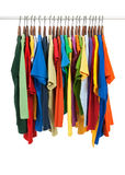 Variety of multicolored shirts on wooden hangers Stock Photos
