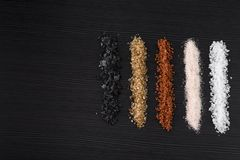 Spicy salt. Variety of natural and spicy salt on black table with copy space royalty free stock photography
