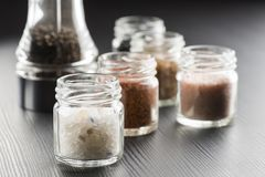 Spicy salt. Variety of natural and spicy salt into glass jars on black table royalty free stock photo