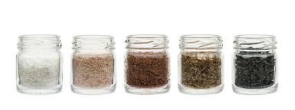 Spicy salt. Variety of natural and spicy salt into glass jars on white background stock images