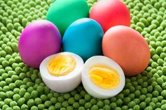 Neon colored Easter Egg still life with cut open hard boiled egg royalty free stock images