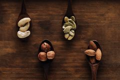 Variety of nuts in dark spoons. On wooden surface stock photography