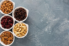 Variety of nuts and dried fruits in small bowls Royalty Free Stock Photos
