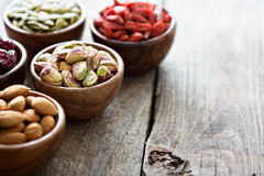 Variety of nuts and dried fruits in small bowls. Variety of nuts and dried fruits in small wooden bowls Royalty Free Stock Photos