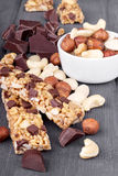 Variety of nuts, granola bars and chocolate on wooden Royalty Free Stock Image