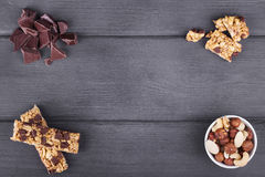 Variety of nuts, granola bars and chocolate on wooden background Royalty Free Stock Photos