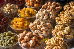 A variety of nuts in plastic bowls in the outdoor market. Healthy food stock photos