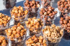 A variety of nuts in plastic bowls in the outdoor market. Healthy food stock image