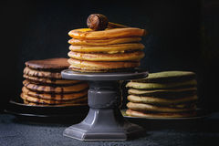Variety of ombre pancakes. Variety of homemade american ombre chocolate, green tea matcha and turmeric pancakes with honey and sauce served on plates and cake Royalty Free Stock Image