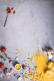 Variety of pasta with tomato sauce and quail eggs. Italian cuisine ingredients over grey background. Copy space, top. View Stock Image