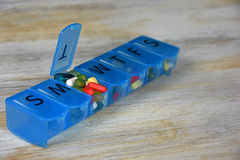 Variety of pills in pill organizer. Variety of pills in a blue plastic pill organizer box Stock Image