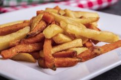 Variety of potatoes for garnish: french fries and sweet potato on a plate royalty free stock image