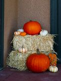 Variety of Pumpkins on Hay Bales - Fall Halloween Decor beside entrance of home royalty free stock photo