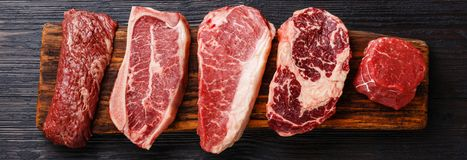 Variety of Raw Black Angus Prime meat steaks. Machete, Blade on bone, Striploin, Rib eye, Tenderloin fillet mignon on wooden board stock photo